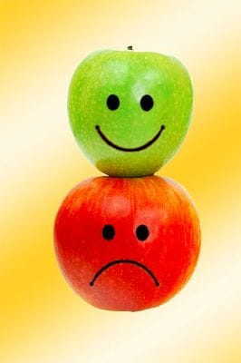 A happy green apple and a sad red apple