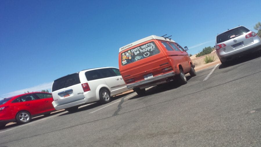 """Van in parking lot with """"Dont Worry Be Happy"""" on window"""
