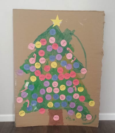 Christmas tree painted on cardboard with paper ornaments