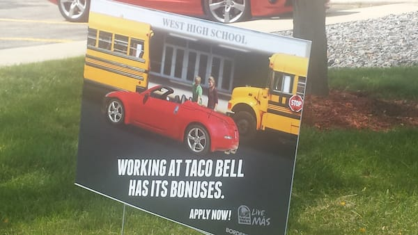 "Taco Bell sign - ""Working at Taco Bell has its bonuses""; includes image of teenage boy standing in front of school buses showing a teenage girl his red convertible"