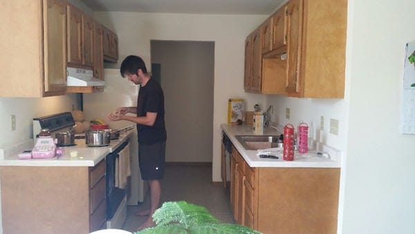 Kitchen in our new apartment - galley style with oak cabinets, older appliances, linoleum flooring