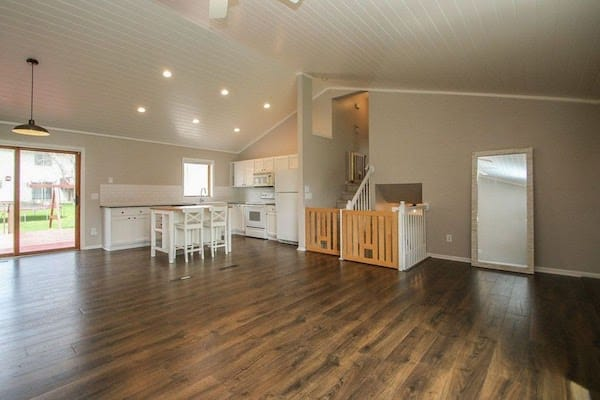 Our remodeled main floor - white plank ceiling, laminate wood flooring, subway tile backsplash, kitchen island, farmhouse sink, custom wood gates