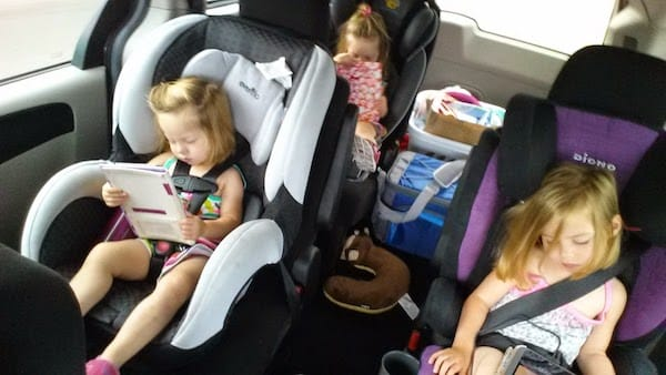 Kids in their car seats looking at tablets