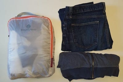 Clothes packed in an organizing bag, jeans and a sweatshirt nearby