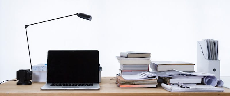 Desk with laptop, lamp, papers, books