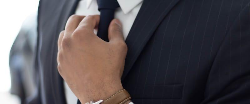 Man in business suit adjusting tie