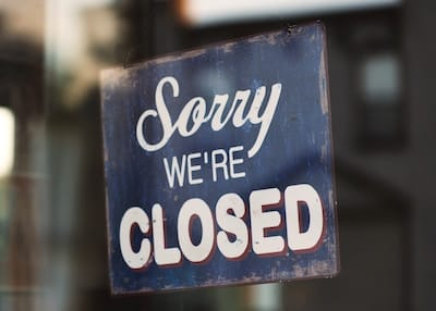 "Sign on shop door with words ""Sorry, we're closed"""