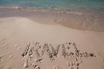 "Sandy beach with the word ""Travel"" written in the sand"