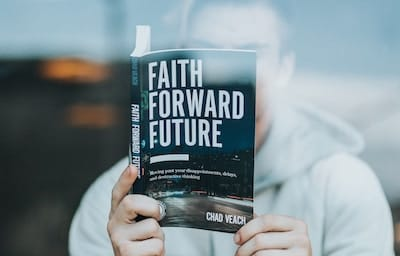 Man reading a book titled Faith Forward Future