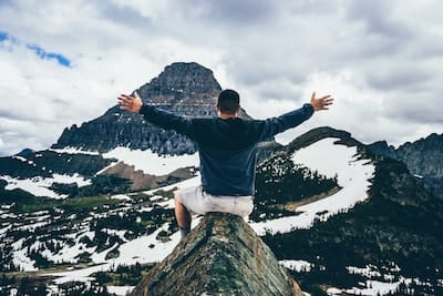 Man on top of a mountain celebrating the view
