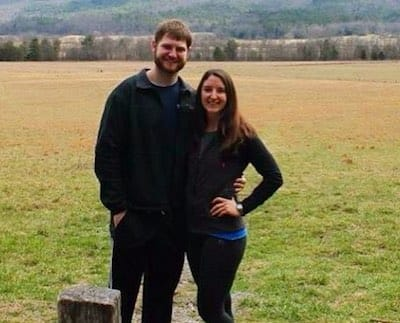 Jared and his girlfriend standing in a grassy field