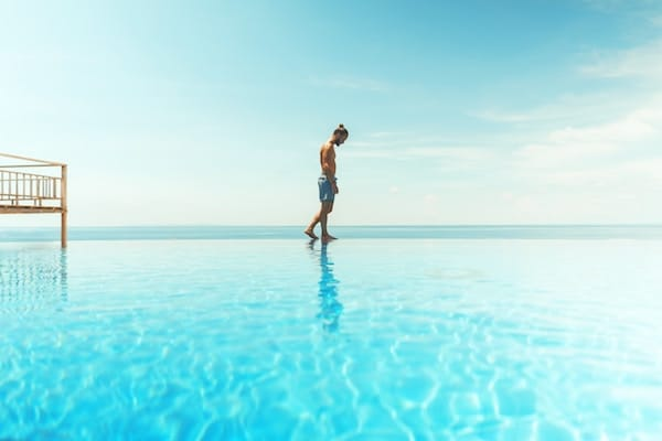 Man walking on edge of pool - appearing as though he's walking on the water