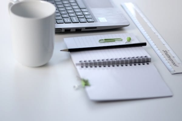 Desk with laptop, notepad, ruler, coffee mug, and pen