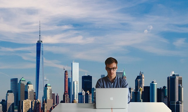 Man working on a laptop with a skyline in the background