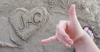 "Sand art at the beach: a heart with ""J+C"" written in it"