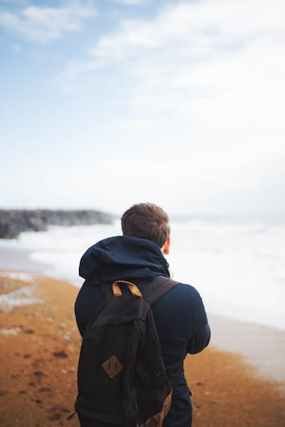A student with a backpack looking out at the coastline