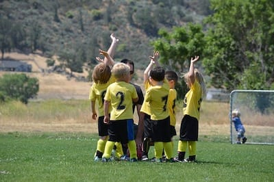 Kids soccer team high-fiving at the end of the game